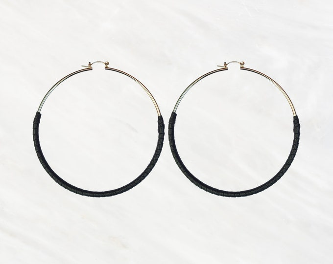 Midnight Skinny Hoops Hand-wrapped in Black Faux Leather. The Perfect Earring to Rock Day and Night. Step Into The Spotlight in These Hoops.