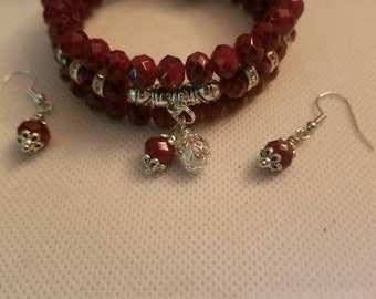 Cranberry faceted beaded bracelet with silver spacer  beads and dangles. Comes with matching earring. 19.99 Free Shipping and Handling