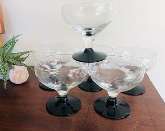 Vintage retro set of 6 clear glass champagne coupes with black glass bases. Etched bowls. All in excellent condition 9cm high. 9cm across
