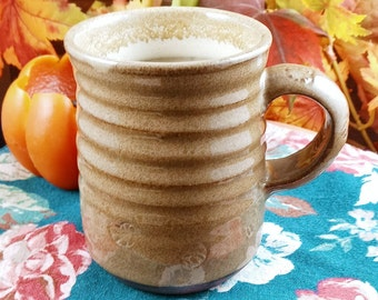 Mottled green stoneware mug. Smooth glazed surface with shell imprint. 8 ounces