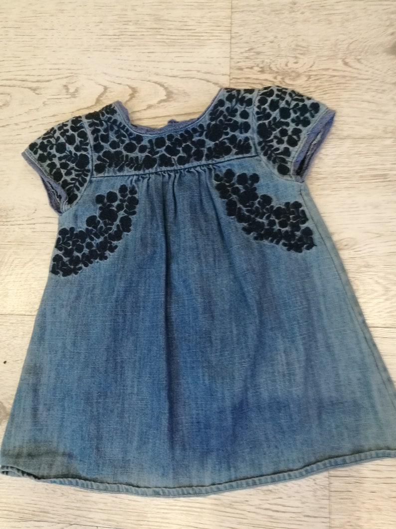 at the front with wrinkles,healthy with botton closure on the back embroidery  with  small sleeves about 1 year Denim dress little girl