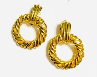 Earings 1980/'s clip on Ornate textured goldtone surrounding a caramel colored acrylic centre.