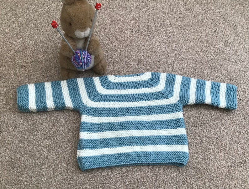 Baby\u2019s hand knitted Breton style jumper in pale blue and white 912 months approx .