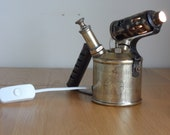 Vintage brass blow torch converted to stylish table lamp with internal illumination small globe bulb.