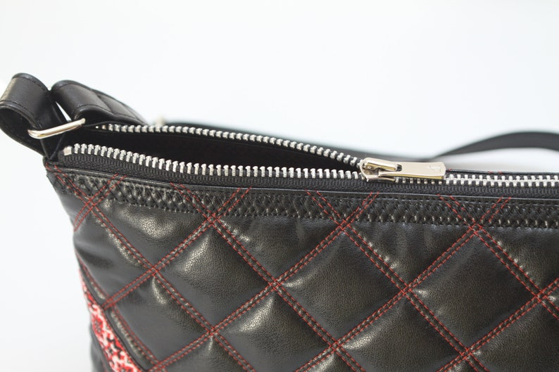 A bright bag made of black leatherette with an embroidered ornament on the top.