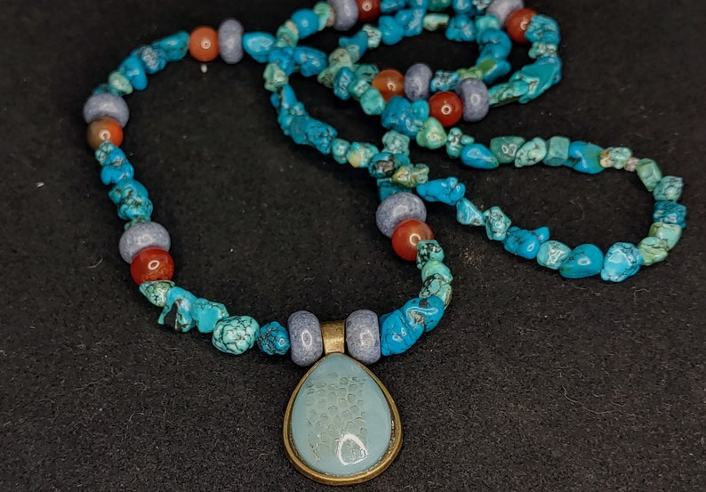 Semi precious stone beaded necklace with snake shed pendant