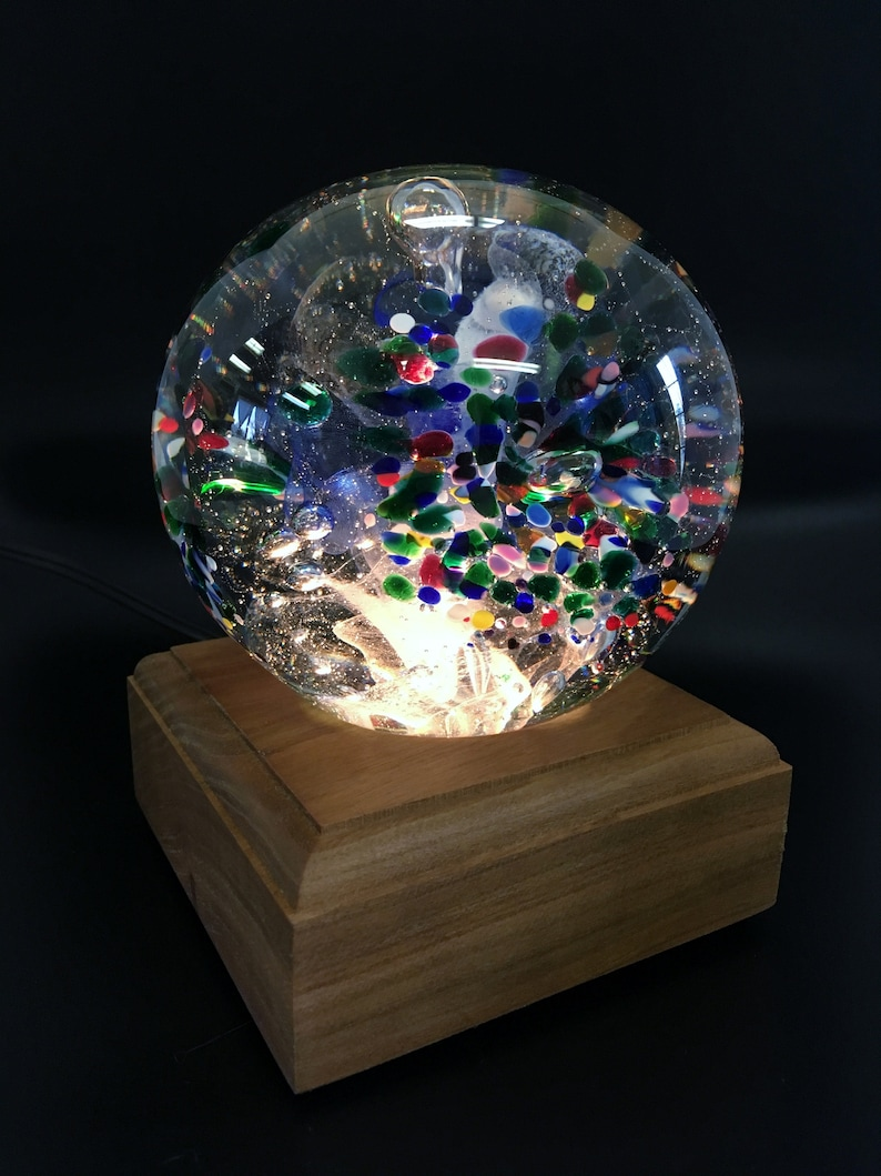 Blue and Red Mix BlueWhite center with Green Blown Glass Large Tri-Flower Paperweight on a Dark Wooden Light Box