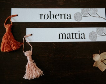 Printed name tag for wedding and events. Black on white paper with pencil drawn flowers. Customizable with colored cotton tassels handmade.