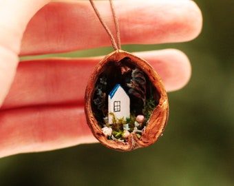 Micro tiny wooden house with floral garden in a shell.