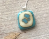Fused glass pendant with reactions of turquoise and blue on french vanilla