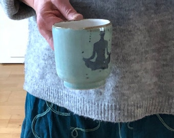 Ceramic mug handmade with handle and yoga/meditation motif. Turquoise with brown border.  250 ml capacity, height 9 cm, width 8.5 cm
