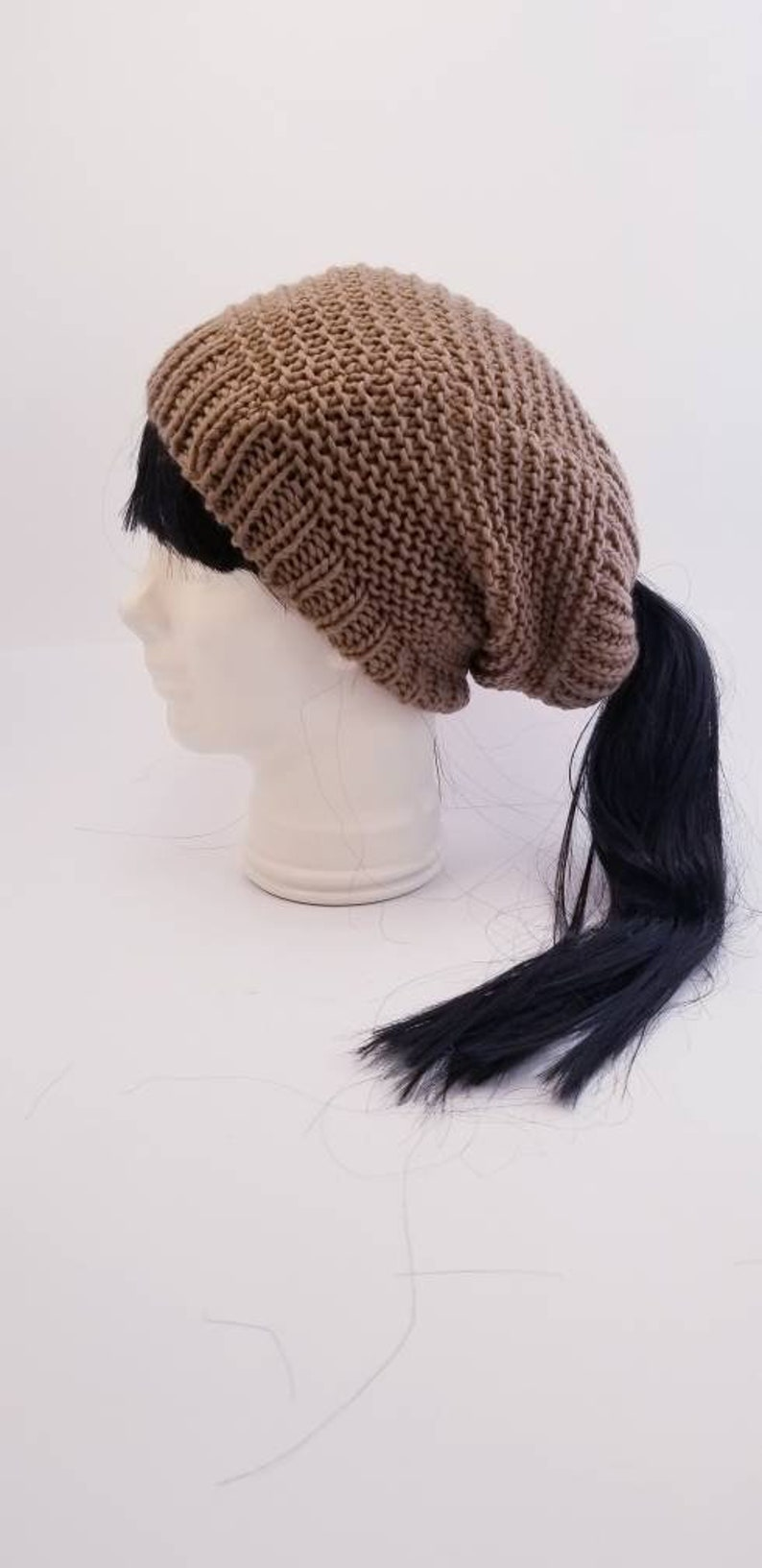 Taupe slouchy beanie with an elastic ponytail top opening great for any winter activity with style the comfort and the warmth.