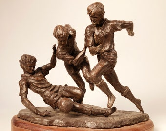 """Soccer: depicts three soccer players at the """"heat of the moment"""" fighting for the ball. The design suggests an imballance/falling over."""