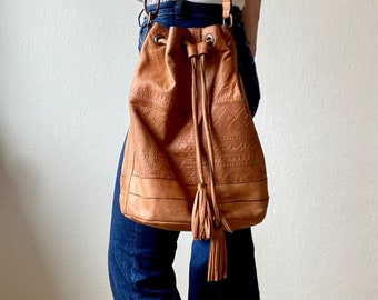 1990s tan brown tooled leather drawstring bucket bag.
