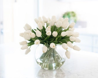 Five Dozen Real Touch Faux Tulips Arranged in a Clear Glass Bubble Vase Set in Water Illusion. Choose from White or Red