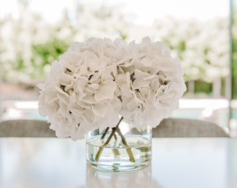 Five Lush Faux Hydrangeas Arranged in a Clear Glass Cylinder Vase and Set in Water Illusion. Choose from White, Blush Pink or Teal Blue