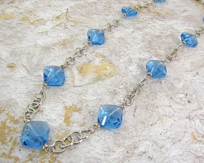 Each glass bead is accented with small crystal spacer beads. Long blue glass beaded necklace with silver plated tear drop shape links