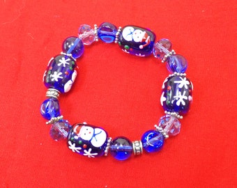 Christmas holiday blue glass beaded stretch bracelet with hand painted snowmen and snowflakes in blue and white enamel