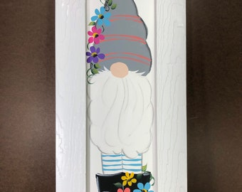 Gnome with spring flowers painted on wood.