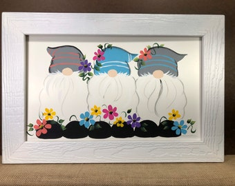 Gnomes with spring flowers painted on wood.