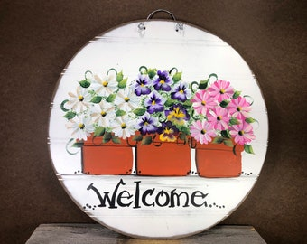 White and pink daisies and pansies in flower pots painted on bead board.