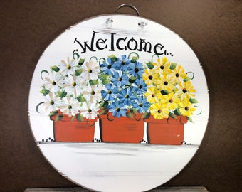 White, blue, and yellow daisies in flower pots painted on bead board.
