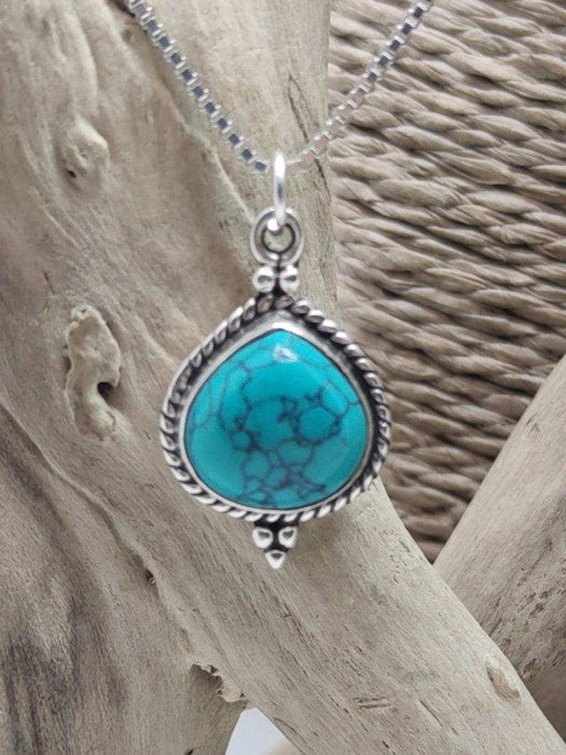 Silver pendant with turquoise stone.