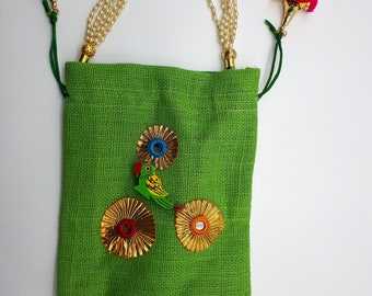 green jute bag with pom poms and parrot