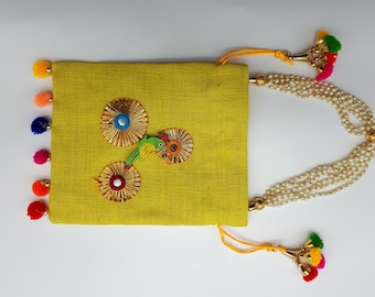 Square bag in yellow jute with pompoms and parrots.