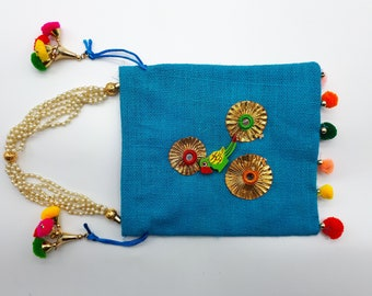 Small square bag in blue jute with pompoms and parrots.