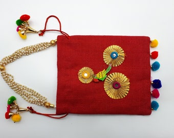 Small square bag in red jute with pom poms and parrots