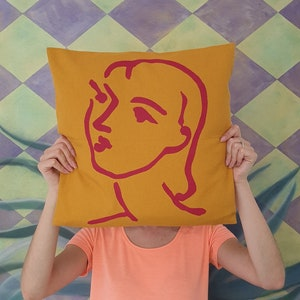 Matisse style Art Cushion Cover drawing of Nadia printed in pink on a red canvas cotton cushion 45 x 45cm