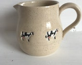 A hand made milk jug decorated with cows. A charming and unique gift.