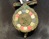 Roman bronze fibula reproduction with emperor Hadrian's center surrounded by colored tiles.