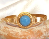 Antique style bracelet with band decorated by players and dancers. Central with blue stone set