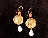 Earrings depicting Tarquinia's alate horses, with coral insert and pearl pendant
