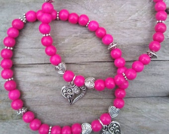Shocking pink handmade beaded bracelet with antique silver heart charm.