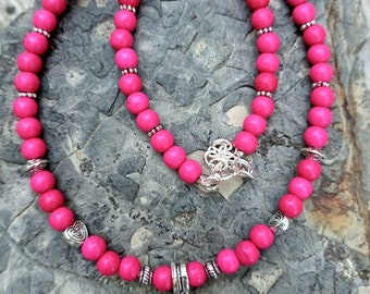 Shocking pink handmade beaded choker necklace with antique silver heart pendant.