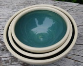 Set of three small nesting bowls. Color is blue/green with an embossed design on the surface