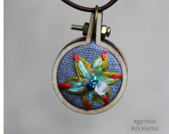 Hand embroidered necklace with beads and fine thread.