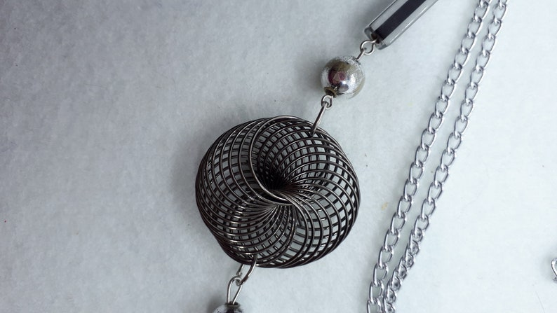 3 twisted wire embellishments. Silvertone chain necklace with silver beads acrylic beads