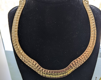 A gold plated necklace from the 60s Mod in hammered metal,collar form
