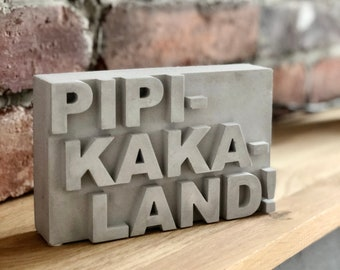 """Concrete signs, various sayings, """"Pipi-Kaka-Land!"""" 