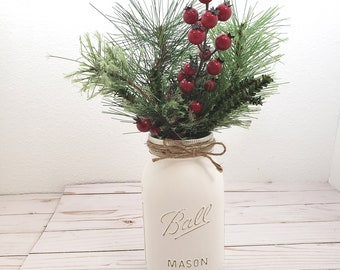 Single quart white painted Mason jars with holiday greens, red berries for Farmhouse Christmas dining table centerpiece & party office decor