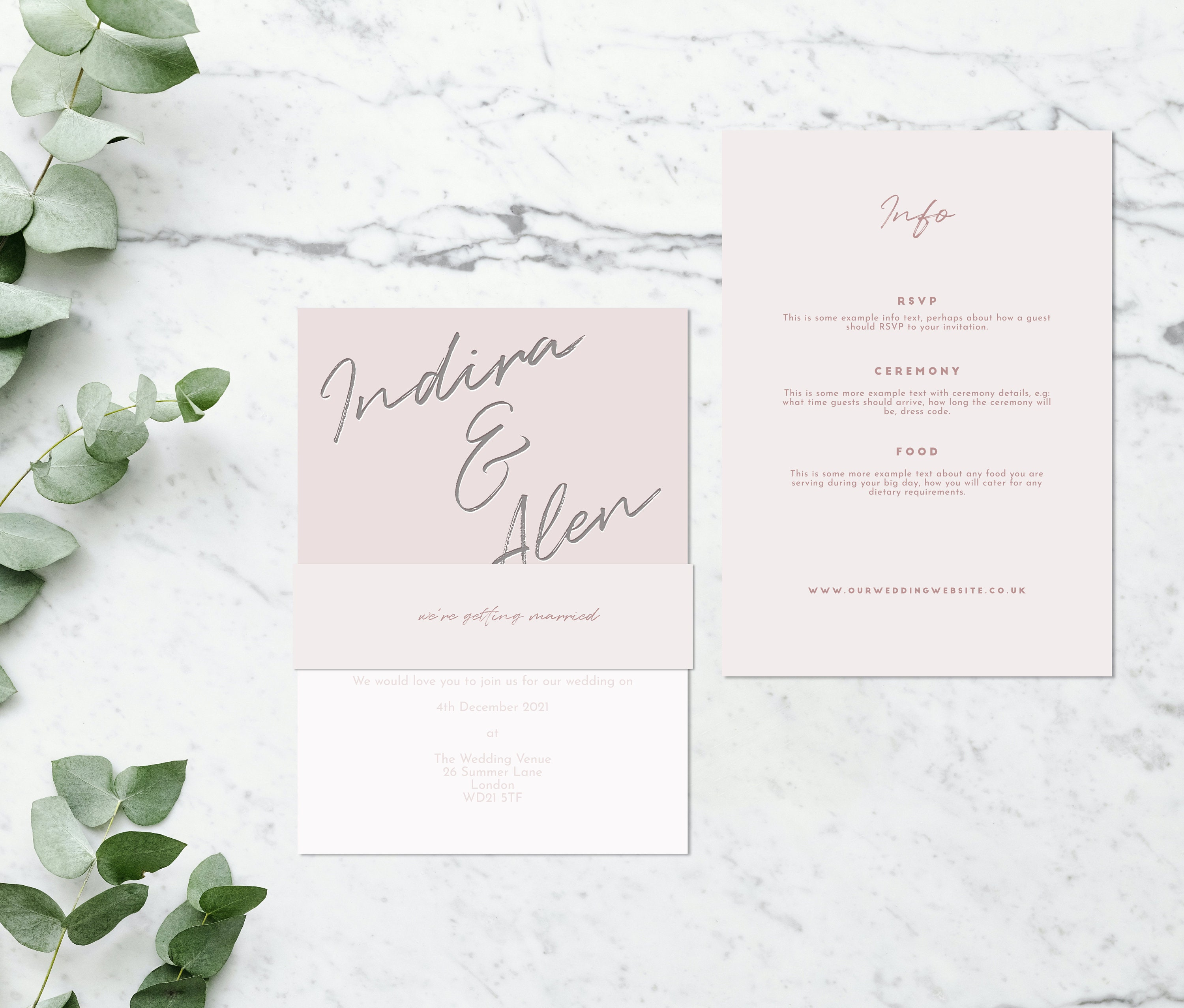 Flat lay photograph of a wedding invitation and information card. The wedding invitation is overlaid with a vellum sheet and wrapped in a belly band. Each card is two-tone blush pink