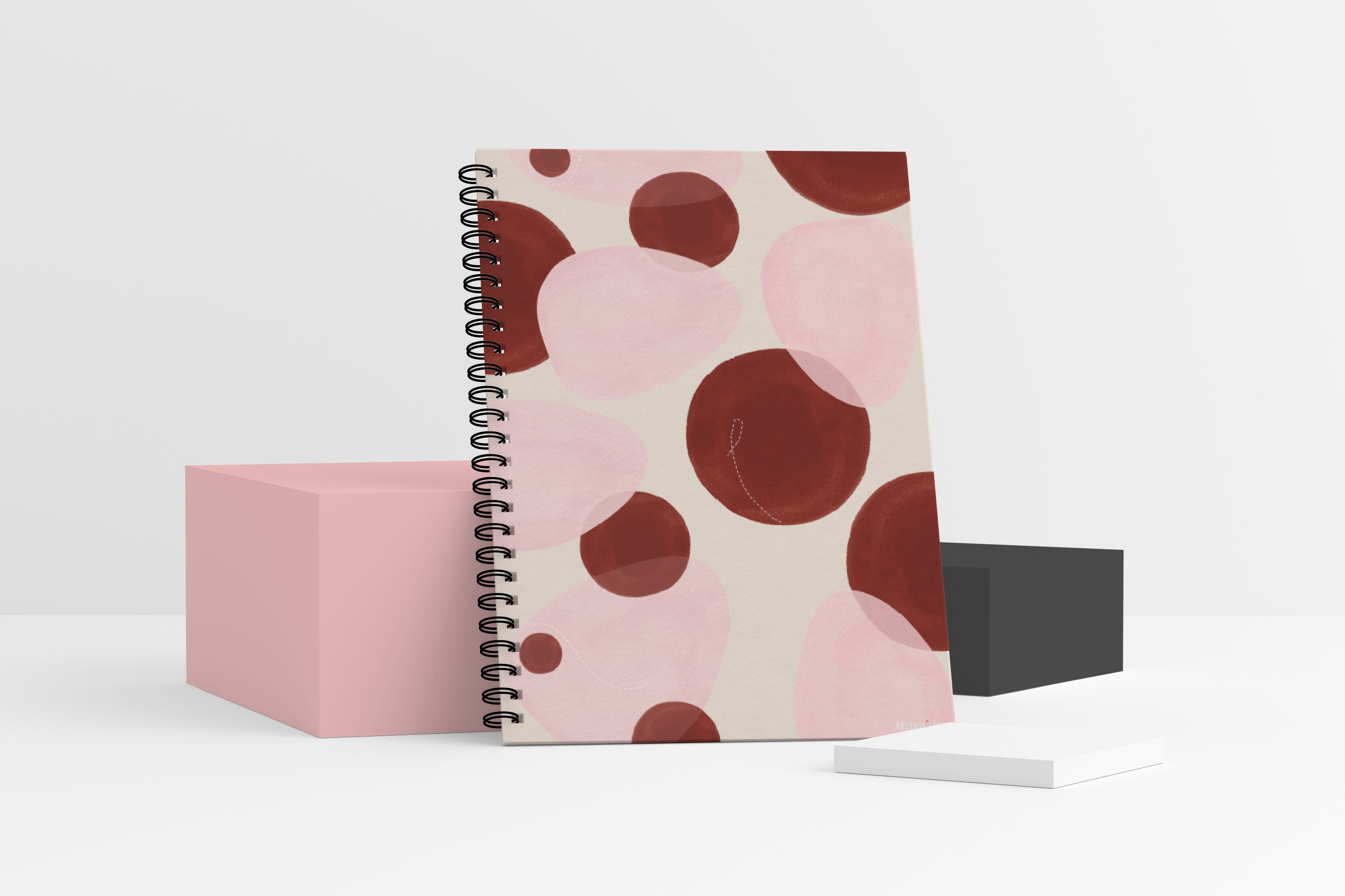 A standing spiral-bound notebook with a pink and red boho abstract design on the front cover