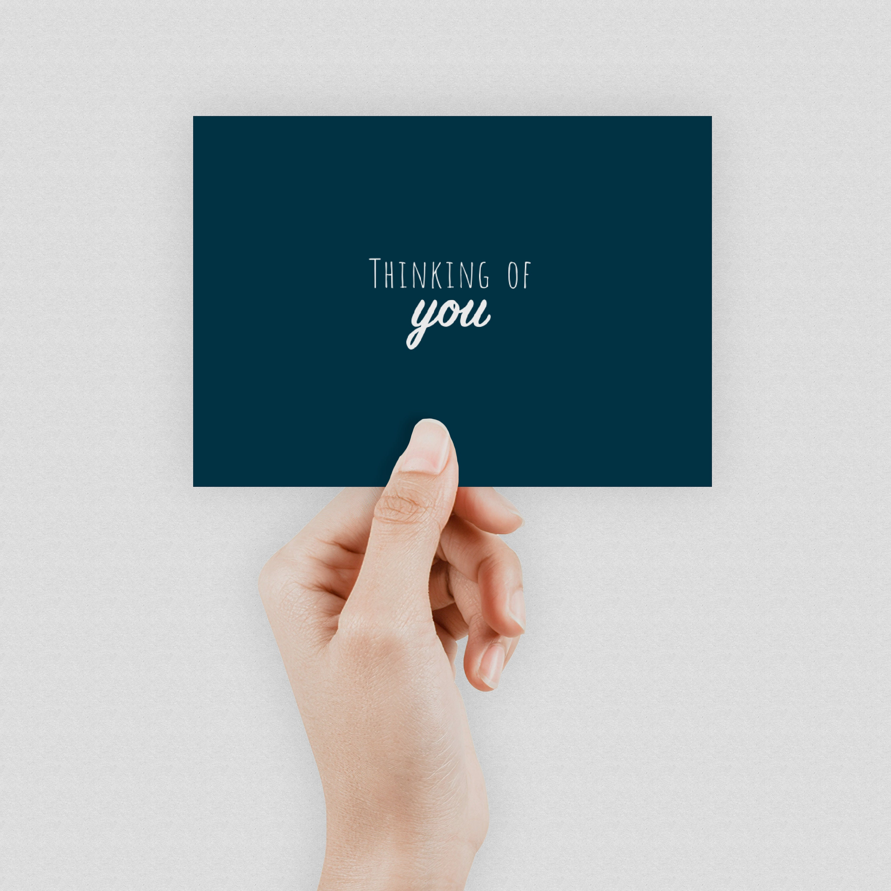 """A hand holding a dark blue postcard which says """"Thinking of you"""" in the middle"""