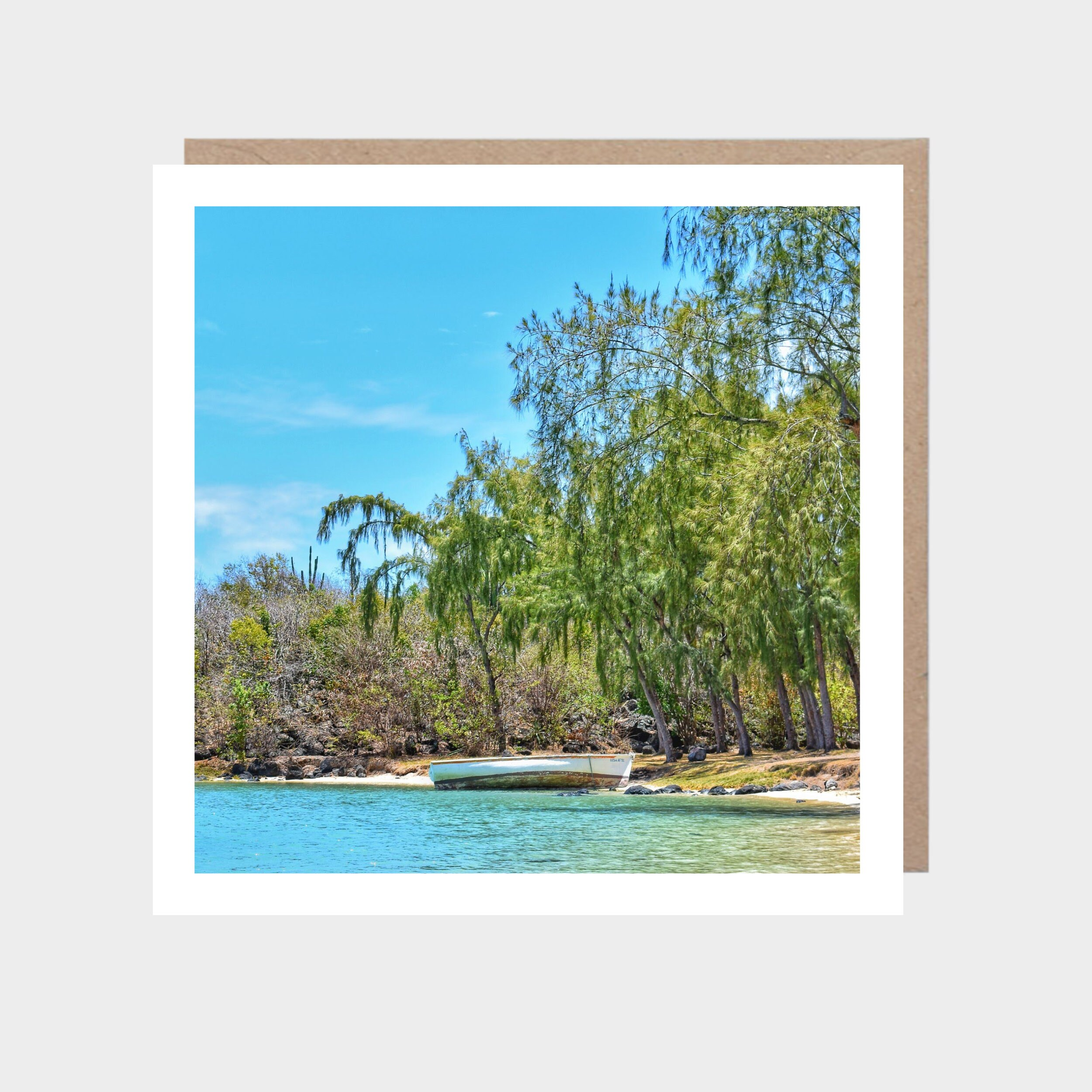Square card with a photo of a beautiful tropical beach, with a brown kraft envelope