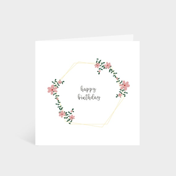 Standing square white card with a gold hexagon, edged with green leaves and pink flowers, and the words 'Happy Birthday' in the middle