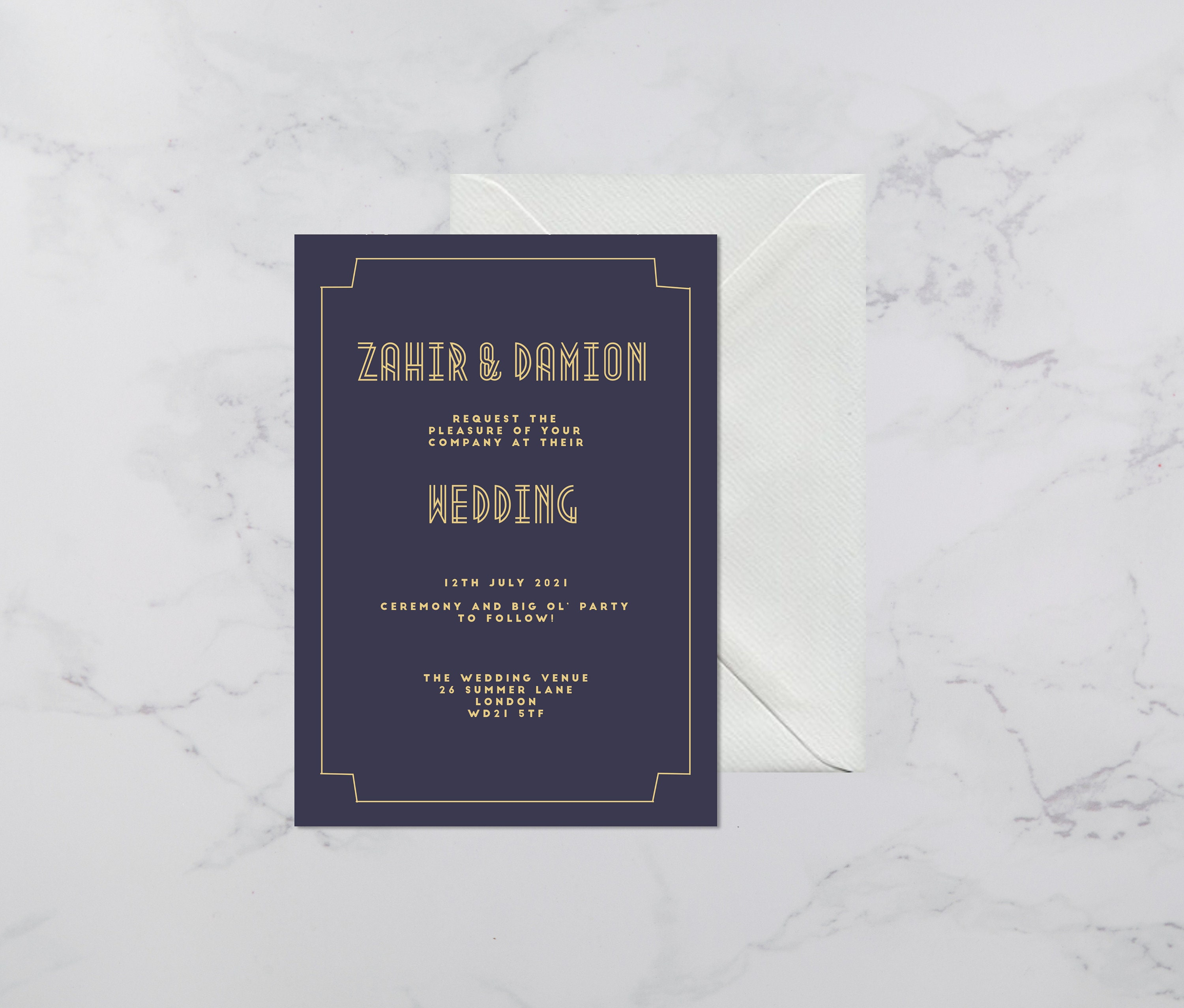 Flat lay photograph of a wedding invitation and white envelope. The design is art deco style, each card is navy card with gold colour details.